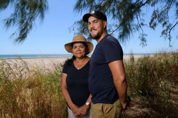 Cian McCue & his mother Camille Damasco standing under a tree with beach in the background