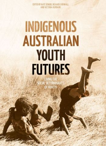 cover of book text 'Indigenous Australian Youth Futures - living the social determinants of health - edited by Kate Senior, Richard Chenhall and Victoria Burbank' sepia photo of two young Aboriginal children in long grass, one attempting a hand stand