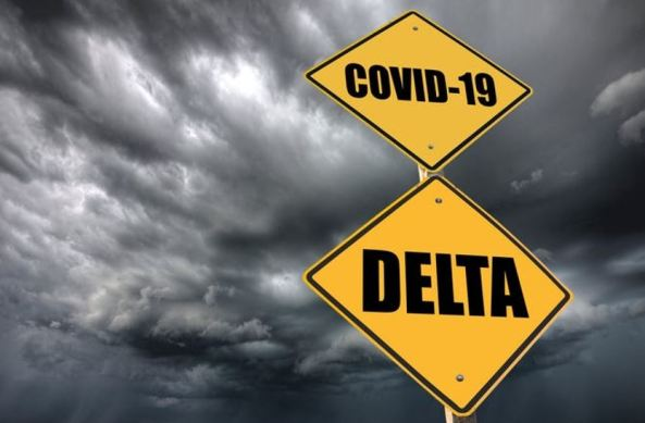 grey storm clouds, yellow signs 'COVID-19' & 'DELTA' black text, same pole