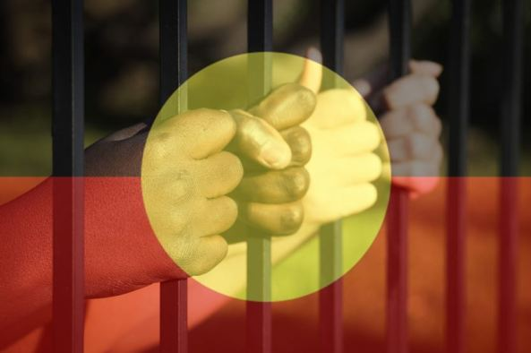 hands gripping jail cell bars, overlaid with transparent Aboriginal flag