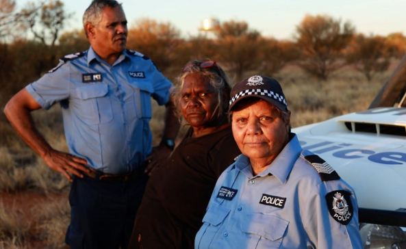 Senior Constable Wendy Kelly, her colleague Revis & Daisy Ward, Ngaanyatjarra Elder standing against police vehicle in outback setting