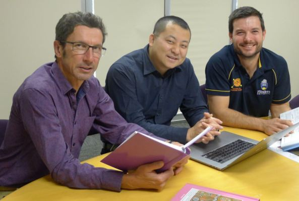 Pharmacy Review Coordinators: Philippe Freidel, Danny Tsai, Tobias Speare sitting at a desk, Philippe & Tobias holding manuals & Danny with open laptop