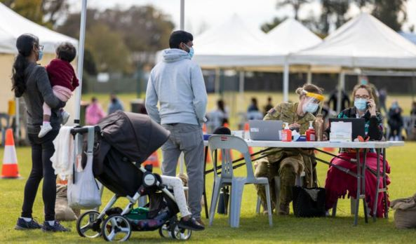 outdoor pop-up vaccination clinic in Dubbo, man, woman, pram with toddler, desk, health professionals under white shade