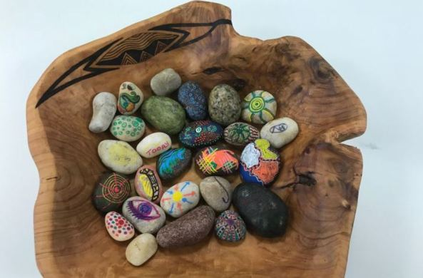 wooden irregular bowl filled with small rocks each painted with Aboriginal art
