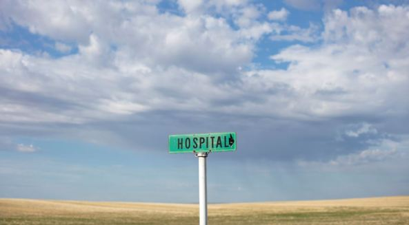 road sign with text 'hospital' against rural scene - wheat field, blue sky