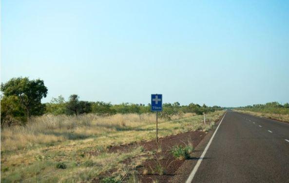 sealed road rural area, blue road sign white medical cross
