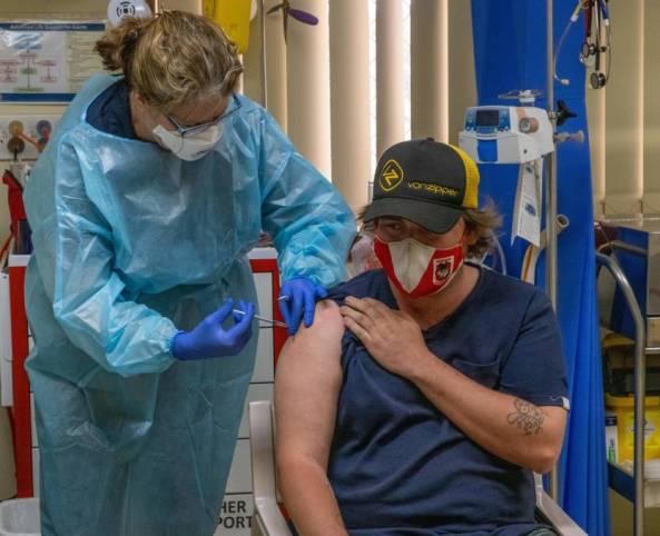 Royal Flying Doctor Service South Eastern Section nurse Caryn Love vaccinates James Hatch at Wanaaring. Image credit: Jason King Media.