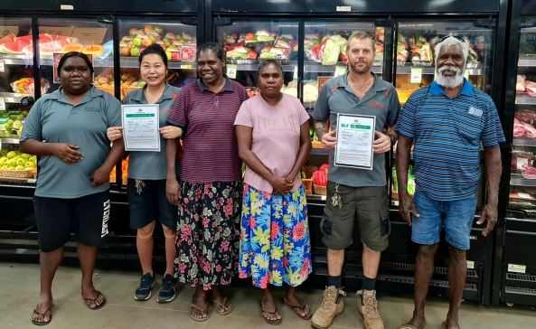 6 Ngukurr Outback Stores staff with certificates standing in front of wall refrigerators