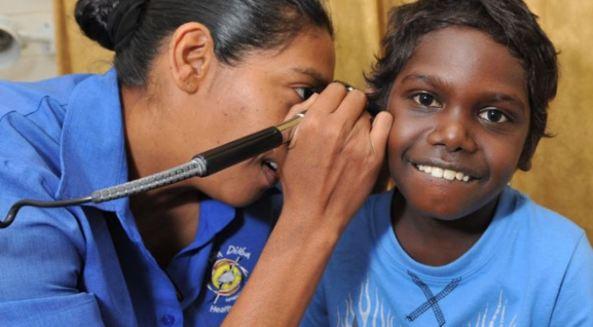Danila Dilba health worker checking child's ear