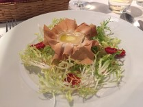 Baked goat cheese with frisée and pine nut salad