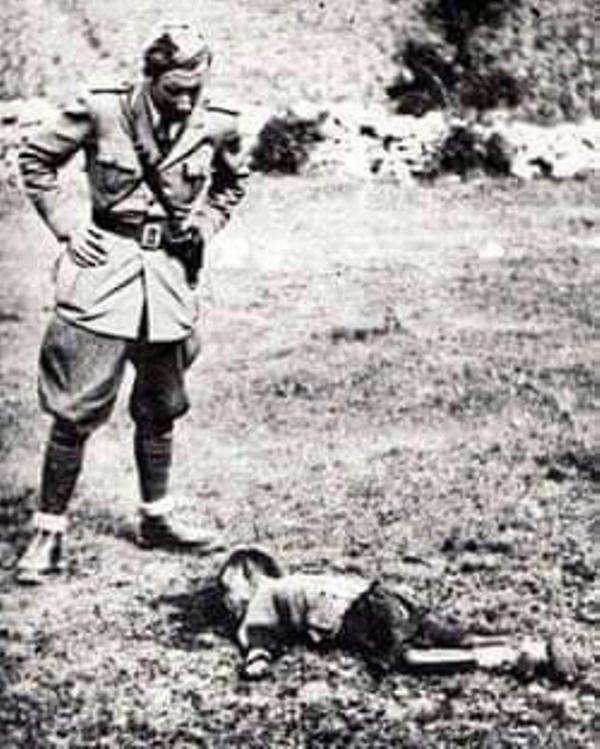 Генерал Александрo Лузанo стоји изнад једнoг прекланог српског детета испред школе у Пребиловцима