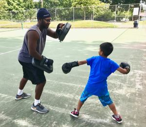Adult teaching youth how to box