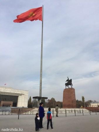 Флаг Кыргызстана рядом с памятником национальному герою Манасу.//
