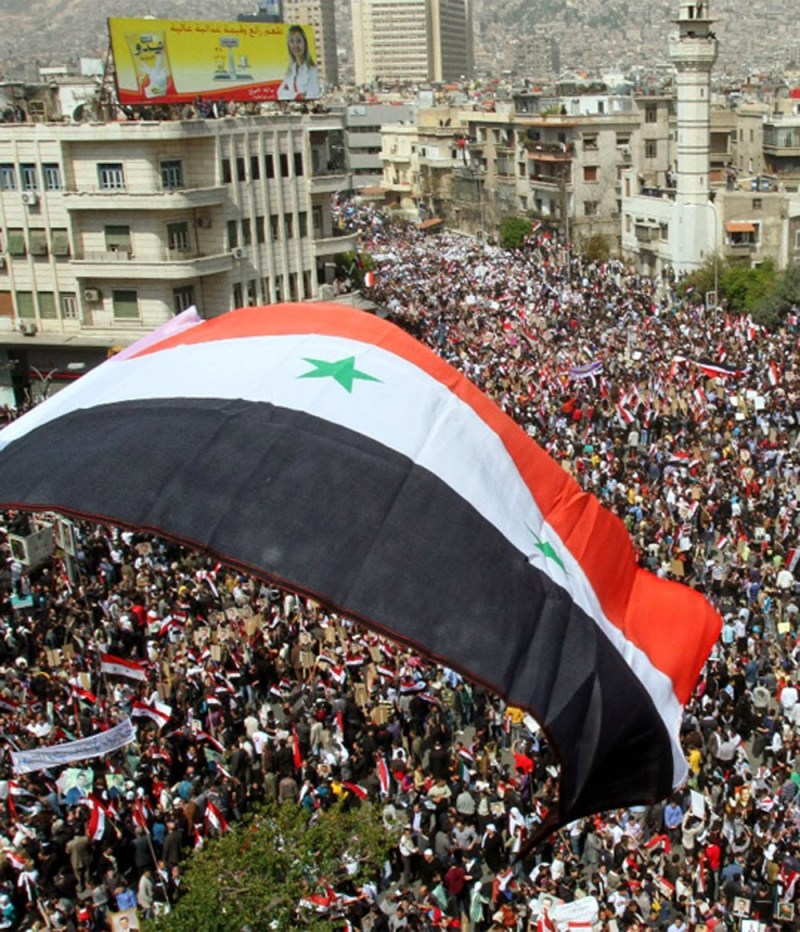 Syria flag waving in crowd of syrian people