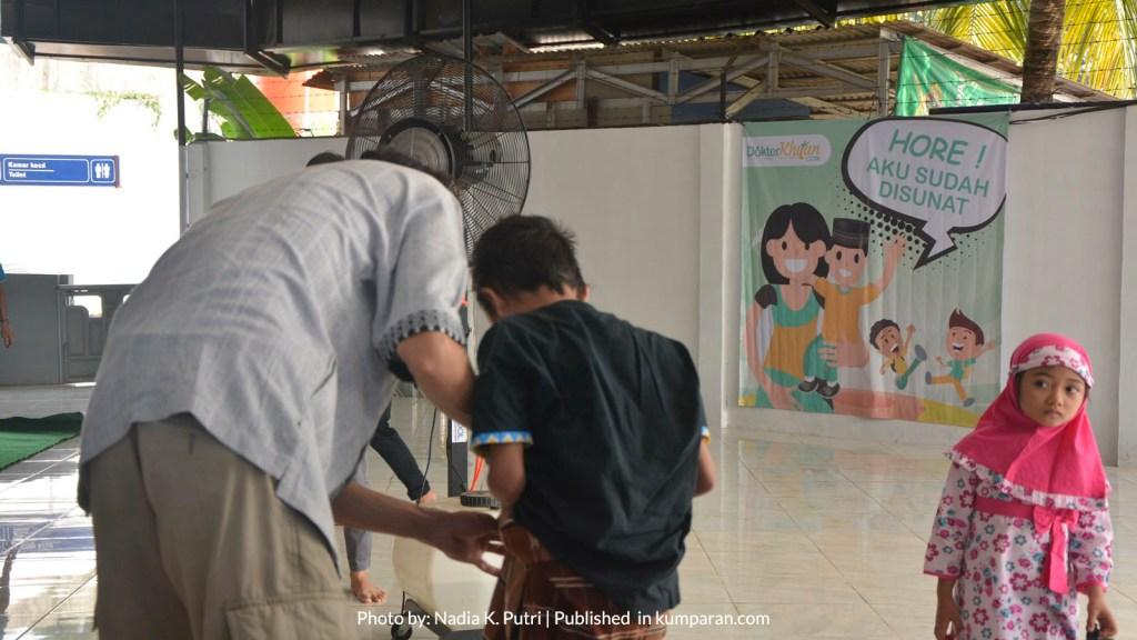Ilustrasi ayah memasangkan sarung anak setelah khitanan massal di Bandara Halim Perdanakusuma, Jakarta (Juli, 2018). Foto: Nadia K. Putri