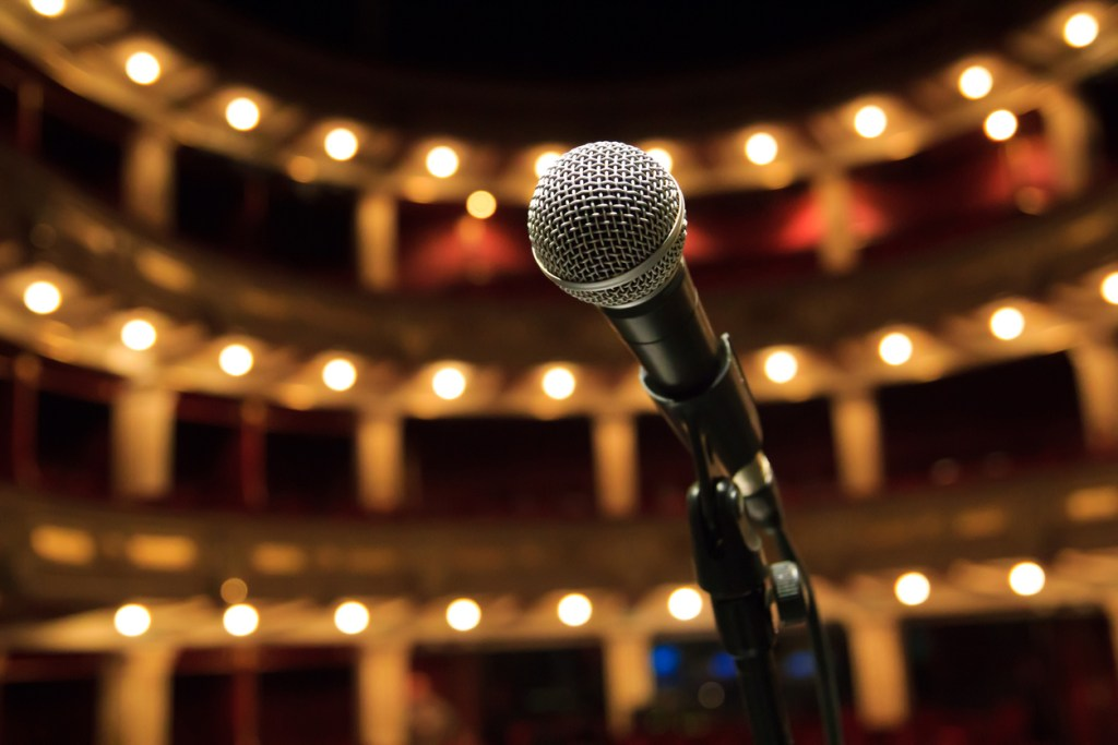 Vocal microphone on stand on stage, looking out into a concert hall