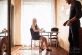 Портрет смеющейся беременной женщины с мужем во время домашней фотосессии.