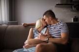 Мама и папа новорождённого целуются во время домашней фотосессии