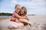 Портрет обнимающихся сестёр на пляже.