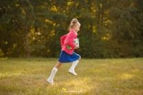 Мини-фотосессия первоклассницы в Риге на фоне леса. Девочка с книгой бежит.
