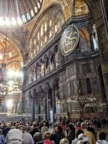 Erdgeschoss, Empore und Teil der Kuppel der Hagia Sophia. Der Blick fällt auf eines der acht hölzernen Rundschilde mit den Namen verschiedener Kalifen (hier: Othman).