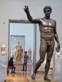 Statue aus dem Antikythera Schiffswrack. Dargestellt ist wohl Paris, Sohn des trojanischen Königs Priamos. Er entführte Helena und löste damit den Trojanischen Krieg aus. Oder die Statue zeigt Perseus, den Sohn des Gottes Zeus in der griechischen Mythologie. Hier zu sehen im Archäologischen Nationalmuseum in Athen.