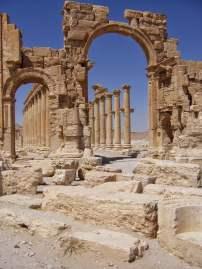 Das Hadrianstor in Palmyra mit der Säulenstraße des einstigen Prachtboulevards der Stadt. An den Säulen befinden sich kleine Basen für heute verschollene Statuen von Geldgebern der Kolonnade und lokalen Eliten.