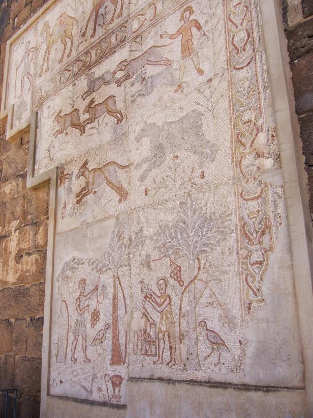 Römisches Mosaik im Zitadellenmuseum von Bosra. Dargestellt ist oben eine Kamel-Karawane, in der Mitte eine Jagdszene mit Hunden und vielleicht Gazellen und unten eine Ernteszene.