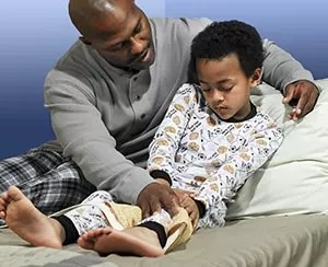 African American father massaging his young son's leg because of growing pains Source: Krames Staywell