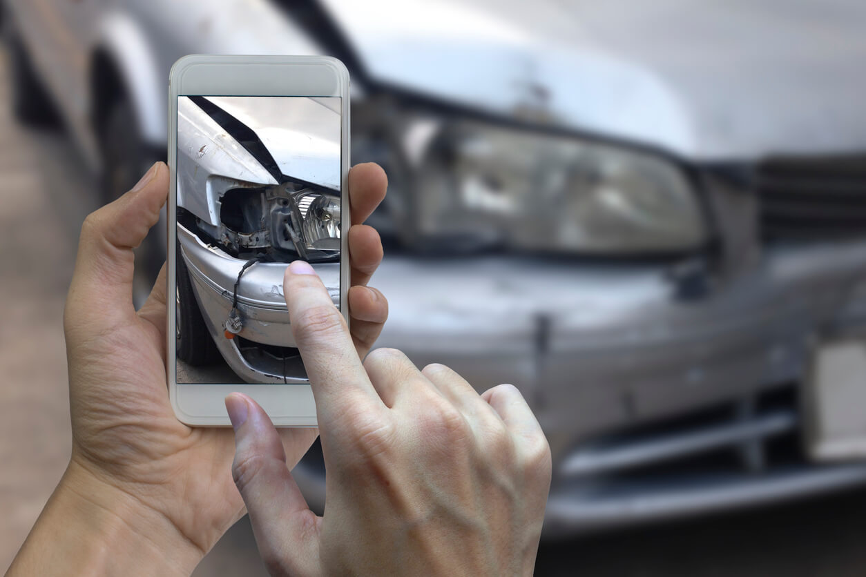 person taking photos of car accident