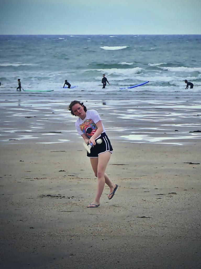 Dziewczyna trenująca hurling na plaży.