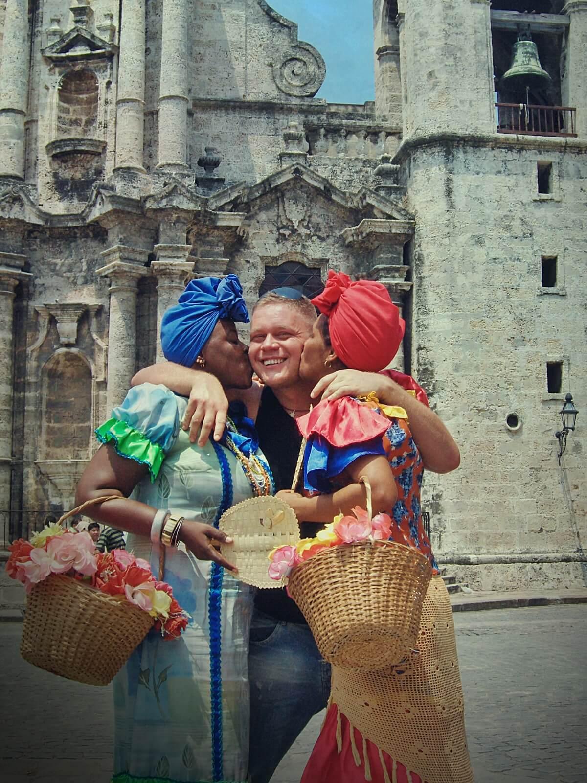 Kubanki z kwiatami całują blogera podróżniczego w Hawanie, na Kubie.