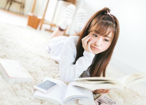 部屋で課題の本を読む女子大生
