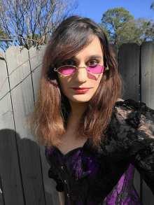 Photo of Naia Okami wearing a purple and black corset and purple shades.