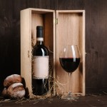 red wine composition with bread bottle in box and wineglass on brown wooden background