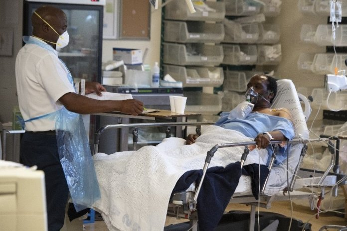 A hospital worker and patient with Covid-19 is seen in in the Resuscitation room of the Covid-19 ward in Khayelitsha.