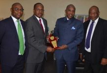 Executive Director, Asset management Corporation of Nigeria (AMCON) Mr. Aminu Ismail (2nd left) presenting the NSITF compliance awards to AMCON Managing Director/Chief Executive Officer, Mr. Ahmed Kuru (2nd right); with them are AMCON Company Secretary/Legal Adviser, Mr. Saidu Jallo (right) and AMCON Group Head, Resolution, Mr. Jushua Ikioda (left) when the AMCON boss received the award in Abuja…Friday
