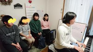 ピアノを弾いている一人の高校生の女の子と、それを聞いている4人の生徒達