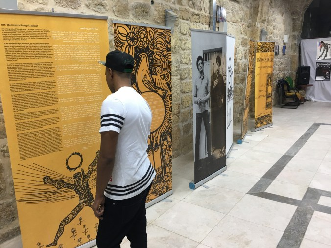 "African community youth reads the bilingual introductory poster for the ""George Jackson in the Sun of Palestine"" exhibit in Jerusalem."