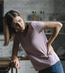 woman with back pain hunched over holding lower back