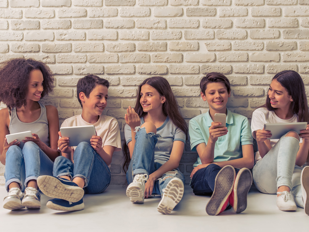 group of teens sitting against wall smiling namaste family services