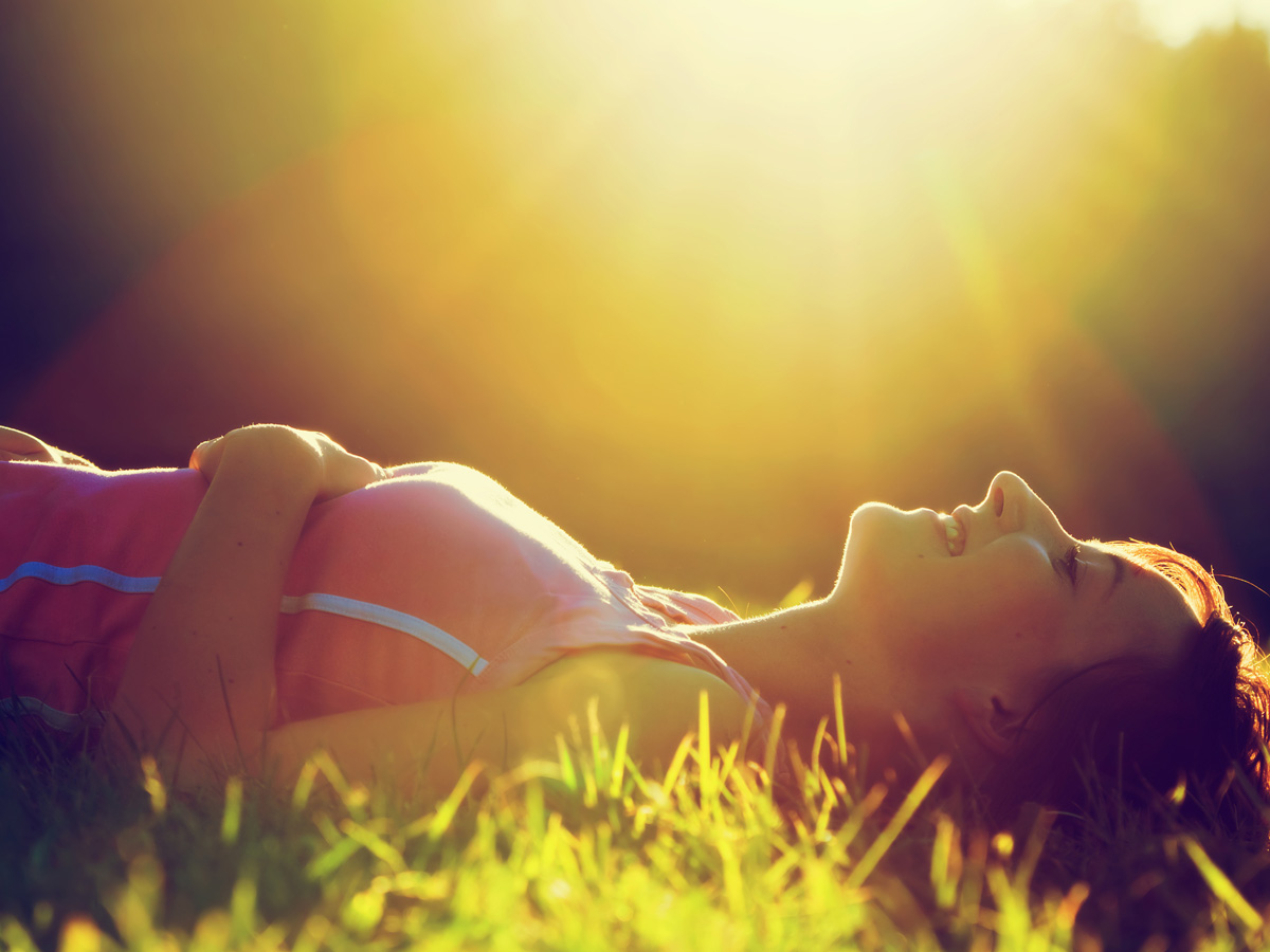 woman lying on the sun smiling namaste family services