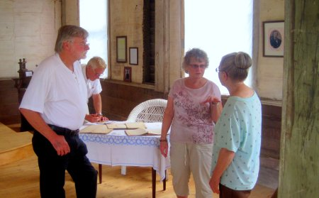 Arlene, pictured on right, discusses the restoration with guests. Original church books are displayed on the table.