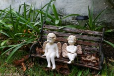 A pair of little angels on a miniature bench keeps a heavenly eye on the garden