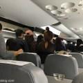 乗降口が空く前の機内の行列