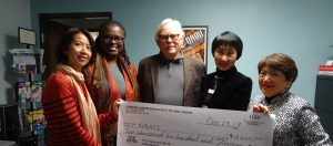 NAMI members stand with people who have donated to NAMI, they hold a large check for 2,600 dollars
