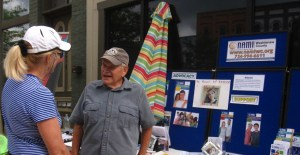A NAMI Member speaks to a member of the public. Behind him, there is a board with information about NAMI Advocacy and Support