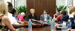 A group of NAMI members sits around a conference table, listening to Senator Debbie Stabinow