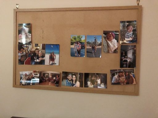 A cork board displaying several 4x6 photos printed and pinned on it.