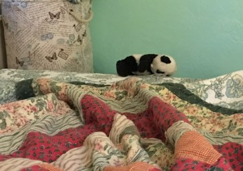 panda balanced on bedframe